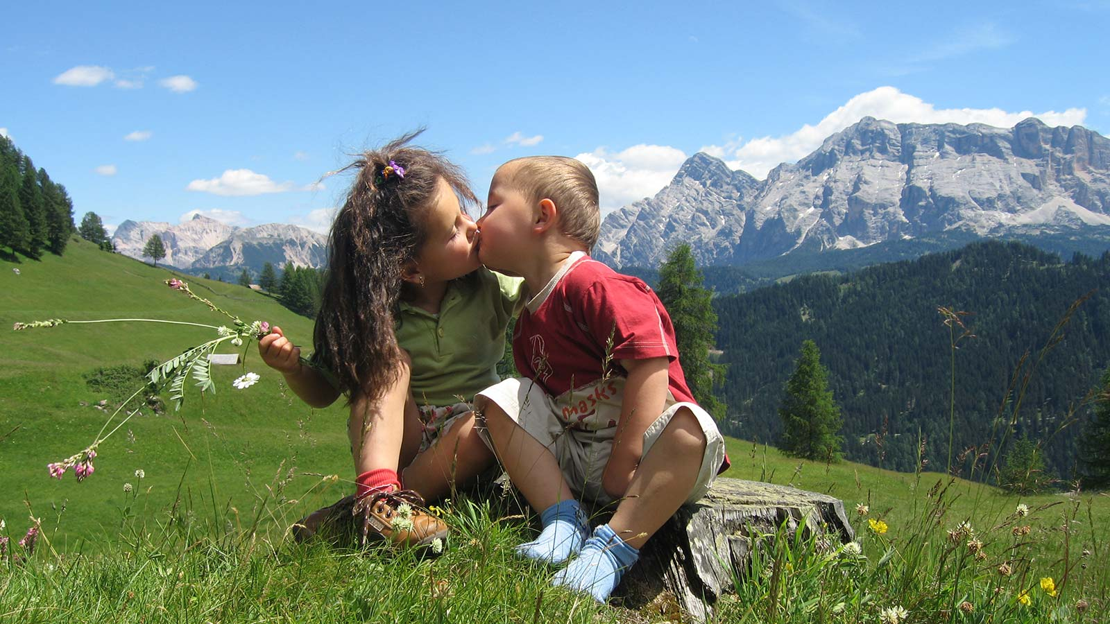 Kids kissing on a mountain meadow with the Dolomites on the background