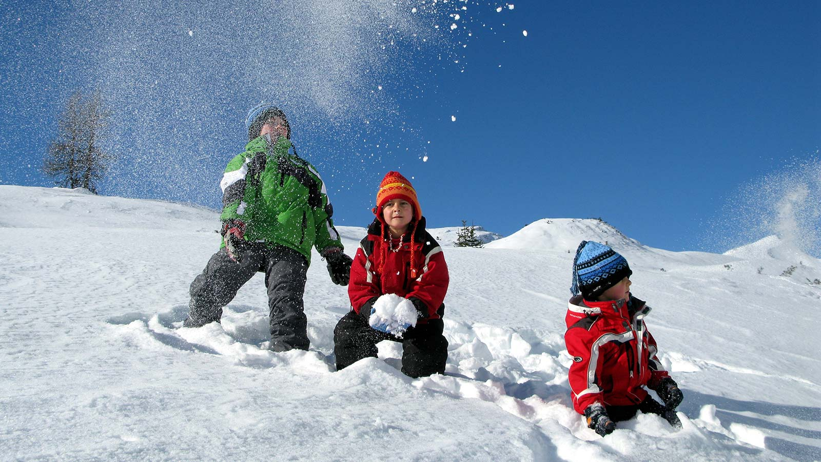 Three kids play in fresh snow in the mountains