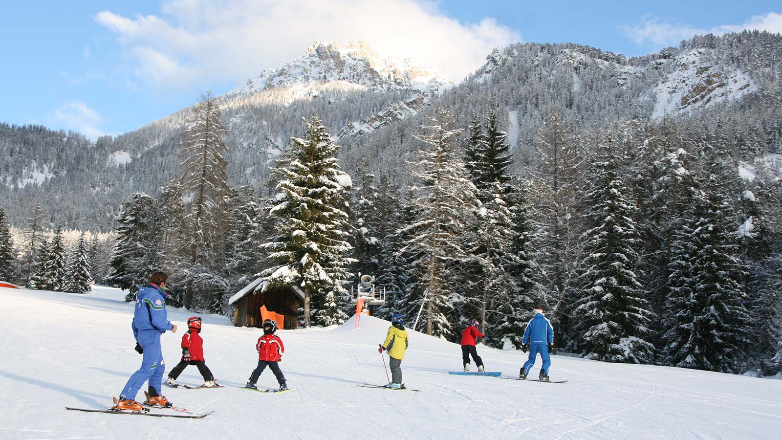 Ski school instructor with little students on San Vigilio di Marebbe's tracks