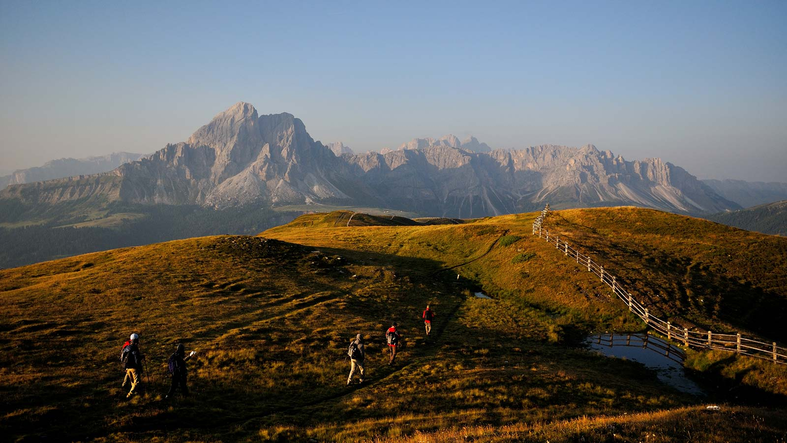 Hikers at twilight in the Natural Park Puez-Odle with Monte Muro on the background