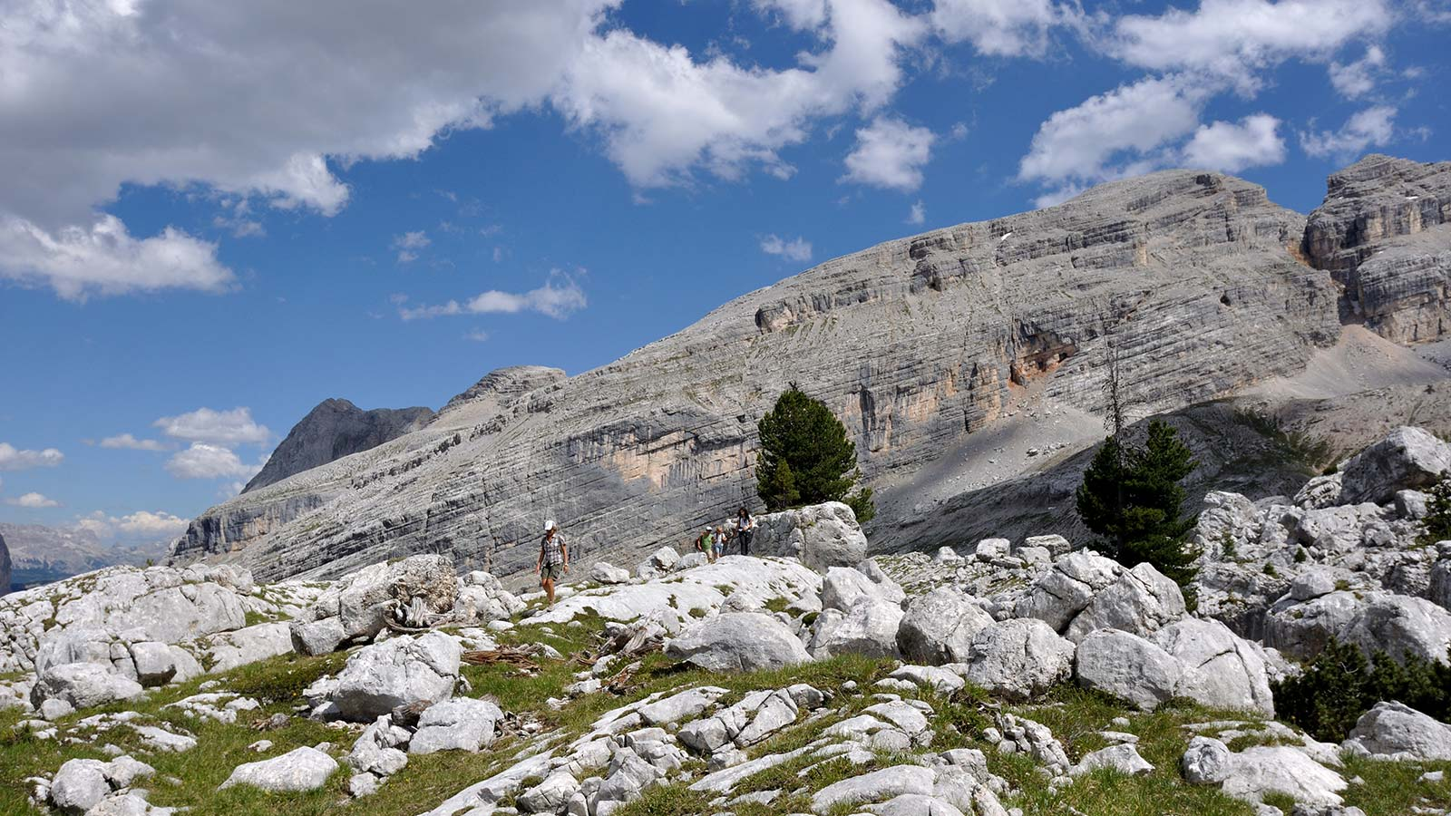 Group of hikers in high mountain walks between the dolomitic rocks in South Tyrol