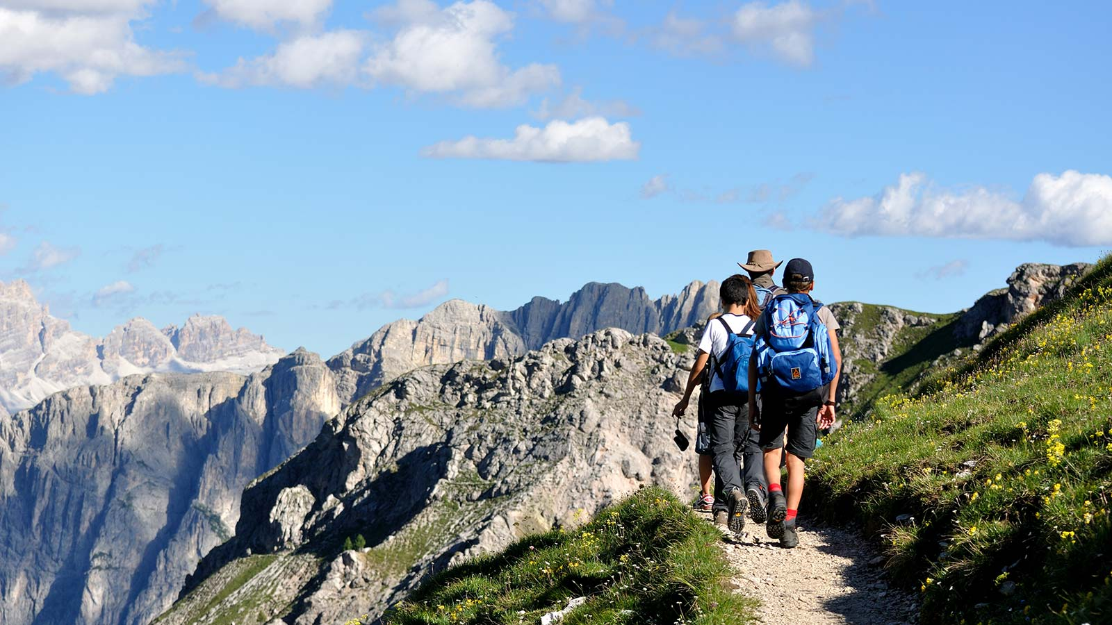 Three hikers on a high mountain path with South Tyrol's Dolomites in the background