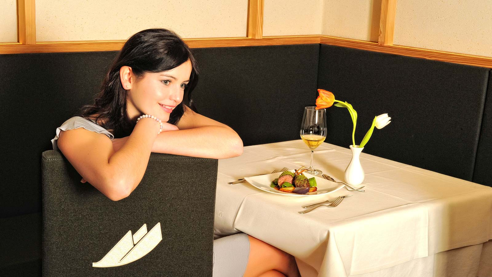 Girl in front of a table with gourmet dish and wine chalice lays her arms on the chair's backrest