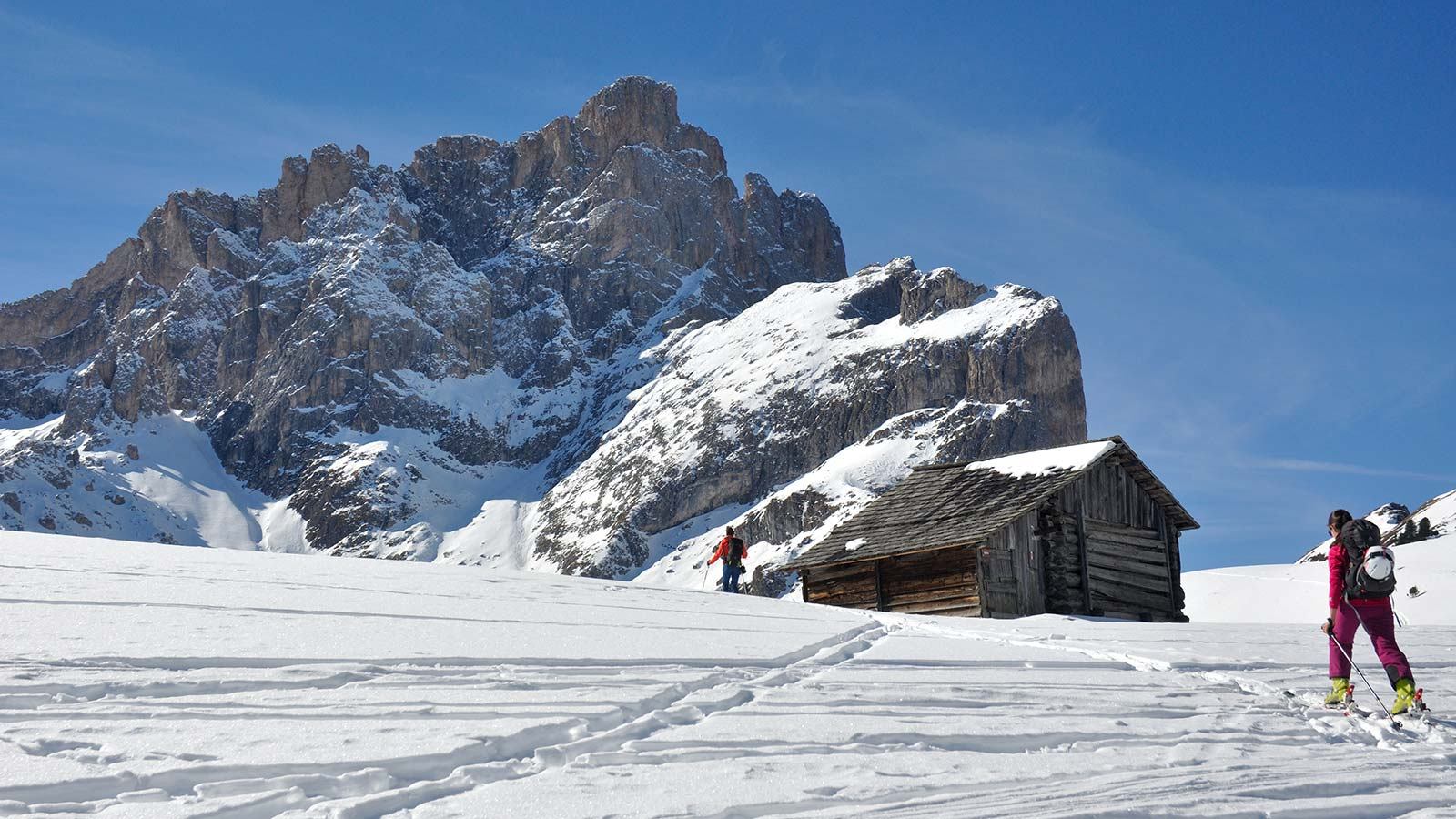 Skier on the Odle of Funes near a wood hut