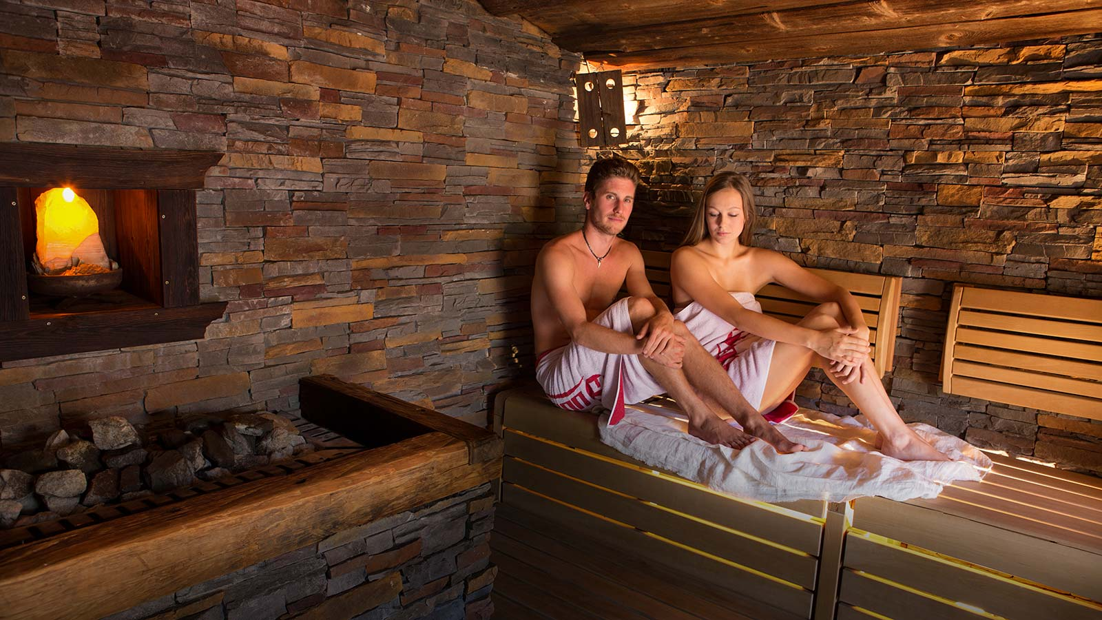 Couple sitting inside the stone and wood sauna at Hotel Teresa