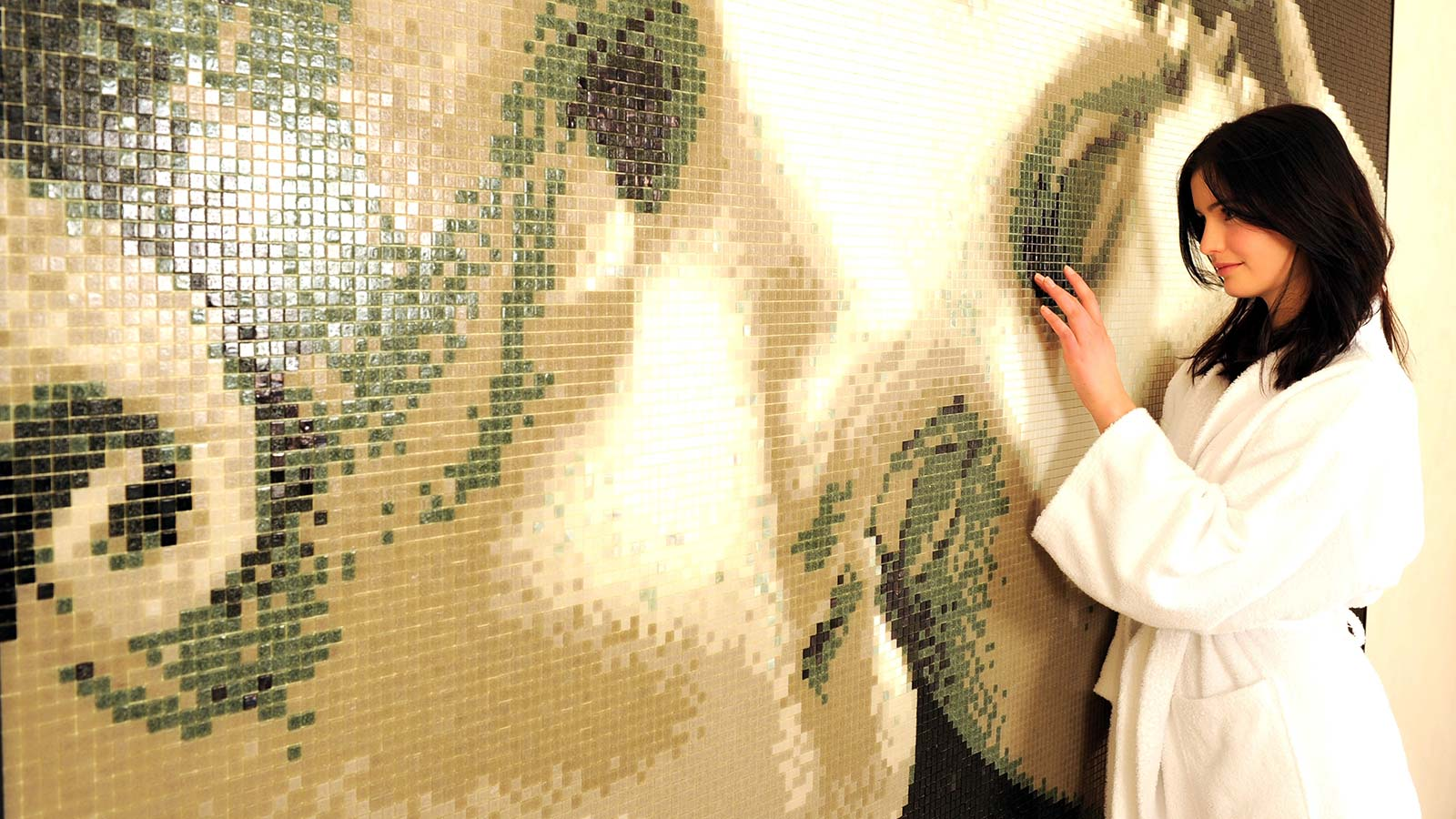 Girl touching the mosaic on the wall of Hotel Teresa's wellness area